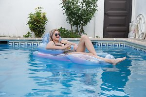 Pretty woman drinking beer in pool