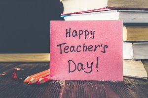 Concept of Teacher's Day. Objects on a chalkboard background. Books, green apple, plaque: Happy Teacher's Day, pencils and pens in a glass, sprig with autumn leaves.
