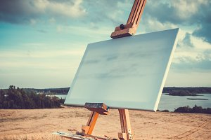 Blank canvas rests on easel outdoors