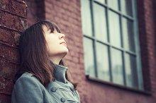 Pensive young girl near brick wall