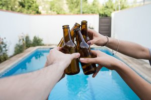 Hands of friends toasting with beer