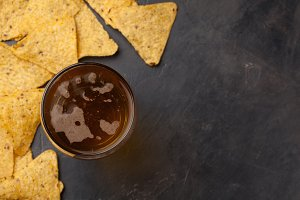 Close-up cold beer in a long glass and of corn Nacho on a dark stone with copy space. Top view