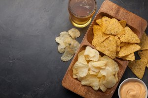 Beer in glasses closeup on the concrete table. Beer and snacks are chips and nachos in wooden bowl with cheese souce. top view. Copy space. Drink and snack for the football match or party