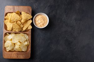 Party snack, chips, Nacho with cheese sauce in a wooden plate on the dark concrete table. top view, copy space