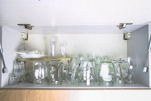 Different glassware in a white closet on the shelf. Banks, jugs, glasses, mugs.