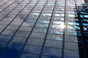 Sun light through blue glass corporate business building architecture background - with copyspace