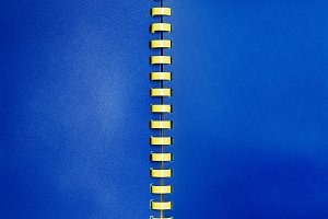 Blue empty notebook with yellow spiral