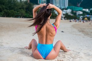 Slender seductive female model relaxing, sitting on the beach with her back to camera