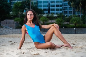 Fit bikini model posing in blue swimwear at paradise beach resort.