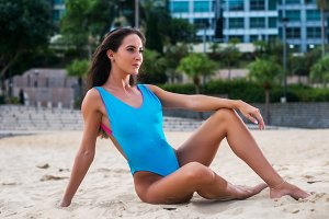 Attractive slender swimwear model posing on sand with resort hotel in the background
