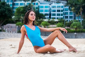 Portrait of beautiful slim girl sitting relaxed on the beach. Caucasian woman  seashore against hotel.