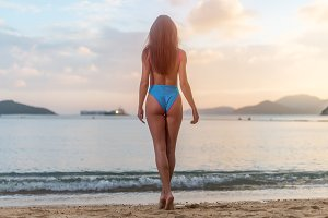 Rear view of sexy sporty young woman standing on the seashore enjoying sunset.