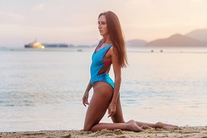 Female fashion model posing in stylish swimwear on seashore at sunset.