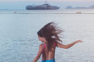 Back view of carefree young woman with her hair streamed running into sea splashing water at sunset  a ship on horizon.