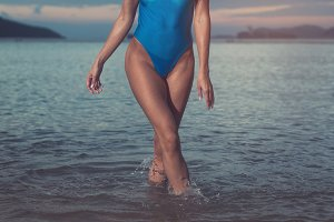 Cropped image of slim young woman wearing trendy blue swimsuit walking in the sea at sunset
