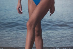 Close-up view of sexy slim female body in blue swimsuit over the sea background in the evening