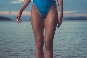 Close-up of female slender legs and body in blue swimsuit standing on beach in the evening with sea in the background