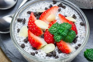 Chia seed pudding with strawberries, almond and chocolate cookie crumbs, on slate board, square format
