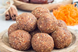 Healthy homemade paleo energy balls with carrot, nuts, dates and coconut flakes, on a wooden plate, square format