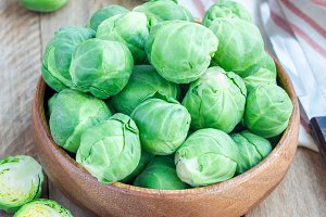 Fresh brussels sprouts in bowl on wooden background, square format