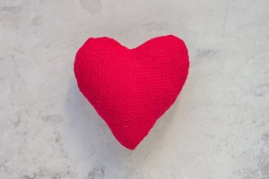 Handmade textile red heart on gray concrete background, square format