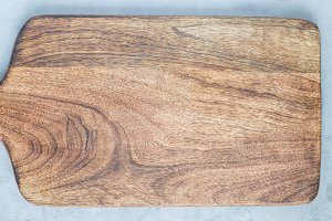 Empty wooden cutting board on concrete background, copy space, top view, horizontal