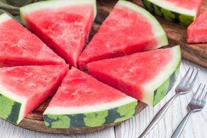 Slices of fresh seedless watermelon cut into triangle shape on wooden plate, horizontal