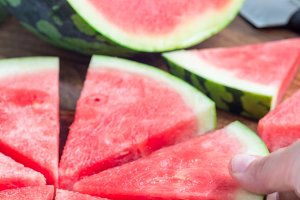 Woman hand take slice of fresh seedless watermelon cut into triangle shape laying on a wooden plate, vertical