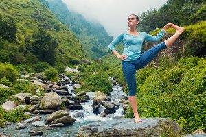 Woman doing Yoga asana outdoors at waterfall