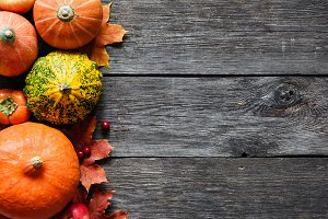 Autumnal background with pumpkins and fallen leaves on wood