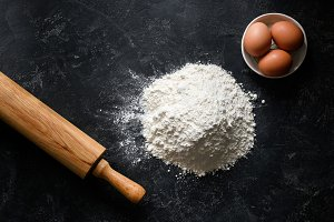 Flour, eggs and rolling pin on dark background