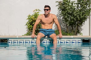 Muscular man posing on poolside