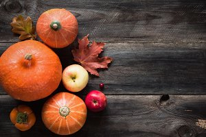 Autumnal background with pumpkins, apples, fallen leaves