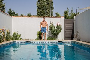 Strong man with sunglasses on pool