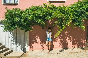 Girl in hat standing near pink wall in Turkish village