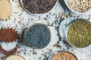 Variety of raw grains, beans, cereals, marble background, square crop