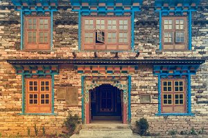 Nepal style windows and door in the old brick wall