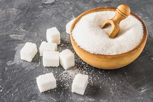 White sugar sugar in a wooden plate with a dustpan on a dark background, cubes of sugar.