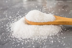 A pile of white sugar sand with a wooden spoon on a dark background.