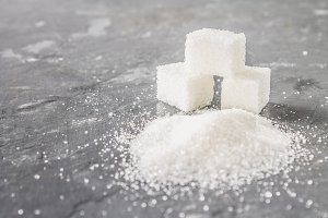 Cubes of sugar and sugar sand on a dark gray background.