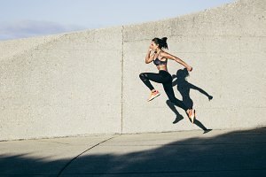 Athletic woman running and jumping