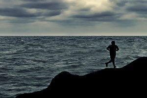 Man Running at Shore of Ocean