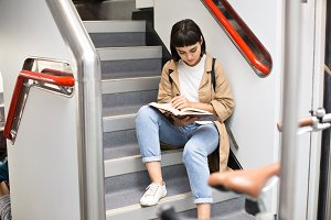 Pretty student reads book on train