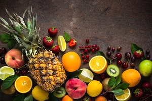 Fruit and berries on dark stone table.