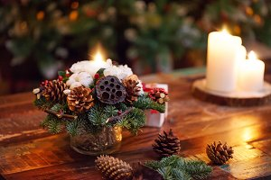 Fir branches decorated for the new year on dark wooden background. Christmas tree and candles, festive mood