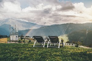 Empty daybeds and rainbow over hills