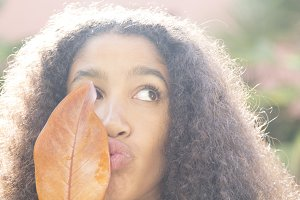 afro girl with leaves in autumn