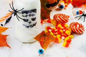 Halloween party set - drinks, candies and decor on white background