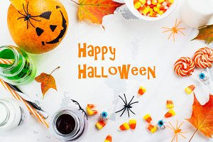 Halloween greeting card - drinks, candies and decor on white background