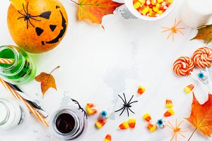 Halloween background with drinks, candies and decor on white table
